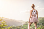 Beautiful young woman on the top of the hill looking at beautiful mountain view.