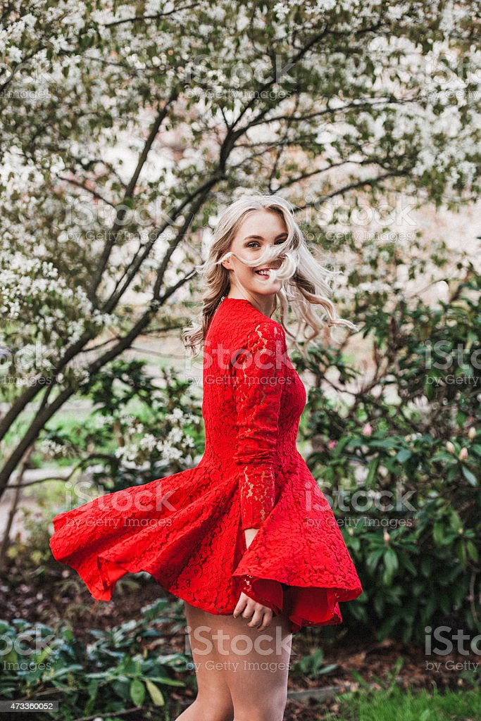 Beautiful young woman outdoors dancing dressed in red stock photo