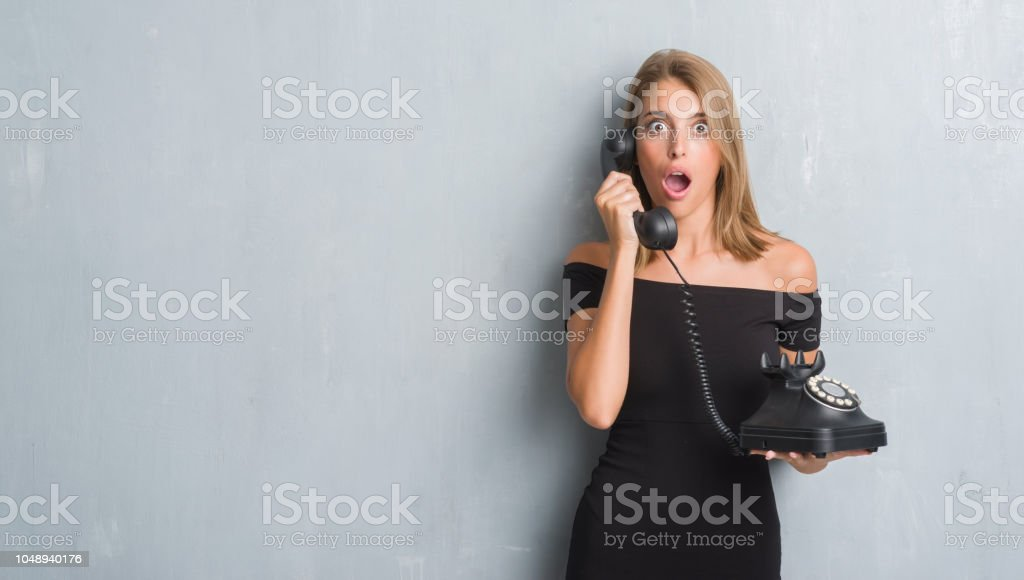 Beautiful young woman over grunge grey wall holding vintage telephone...