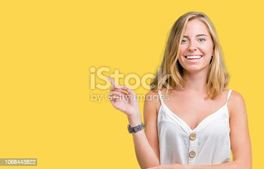 istock Beautiful young woman over isolated background with a big smile on face, pointing with hand and finger to the side looking at the camera. 1068443822