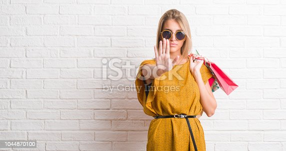 Beautiful young woman over white brick wall holding shopping bags on sales with open hand doing stop sign with serious and confident expression, defense gesture