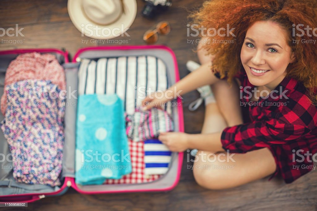 Beautiful young woman with long red curly hair packing suitcase for a...