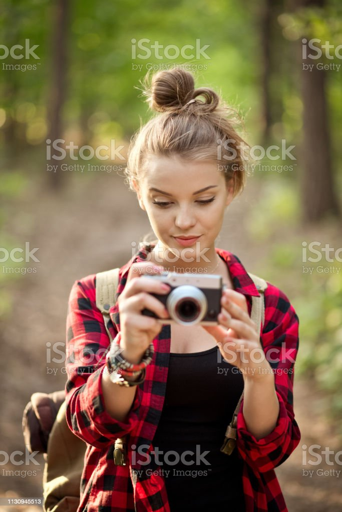 Beautiful young woman photographing in forest Beautiful young woman photographing with digital camera. Blond hipster is hiking in forest. Female explorer is with hair bun. 20-24 Years Stock Photo