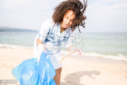 962184460 istock photo Beautiful young woman picking up garbage during local clean up 962182098
