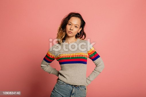 Young woman dressed in a striped sweater in front of a pink background.