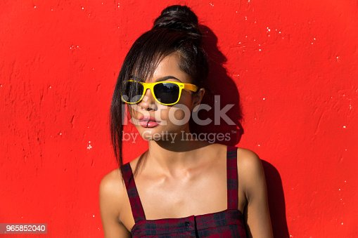 Beautiful young woman standing in front of red background.