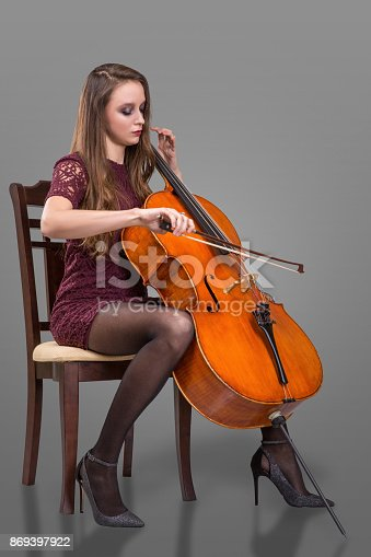 Beautiful young woman sitting on the chair and playing cello. Isolated on grey background
