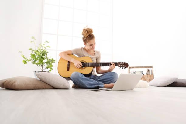 コンピューターでは、美しい若い女性ギター オンライン コースによって、家庭でのカジュアルな服で床に座って弾くことを学ぶ - ギター ストックフォトと画像