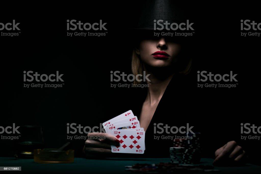 Beautiful young woman playing poker stock photo