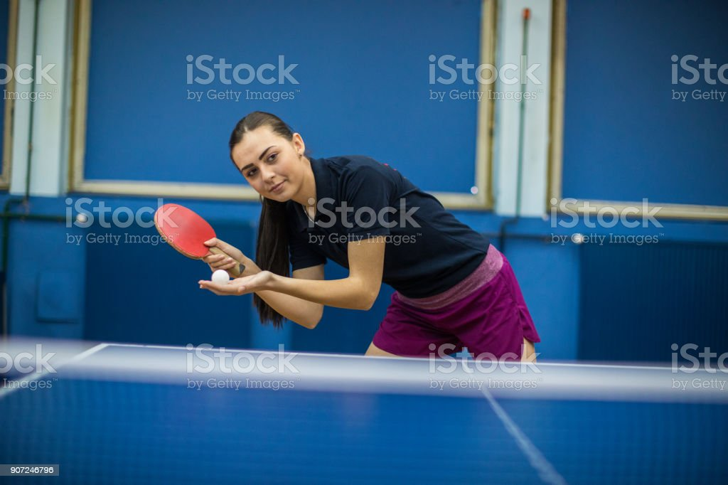 Beautiful young woman playing table tennis stock photo