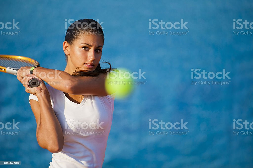 Beautiful young woman playing tennis stock photo