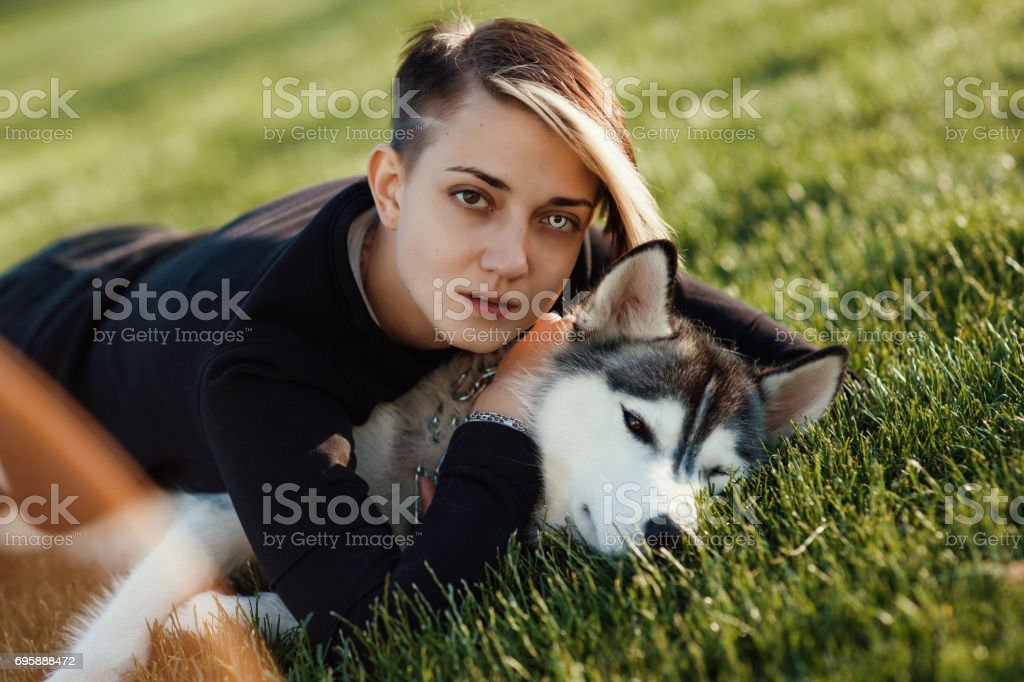 Schöne junge Frau mit lustigen husky Hund mit anderen Augen draußen im Park spielen – Foto
