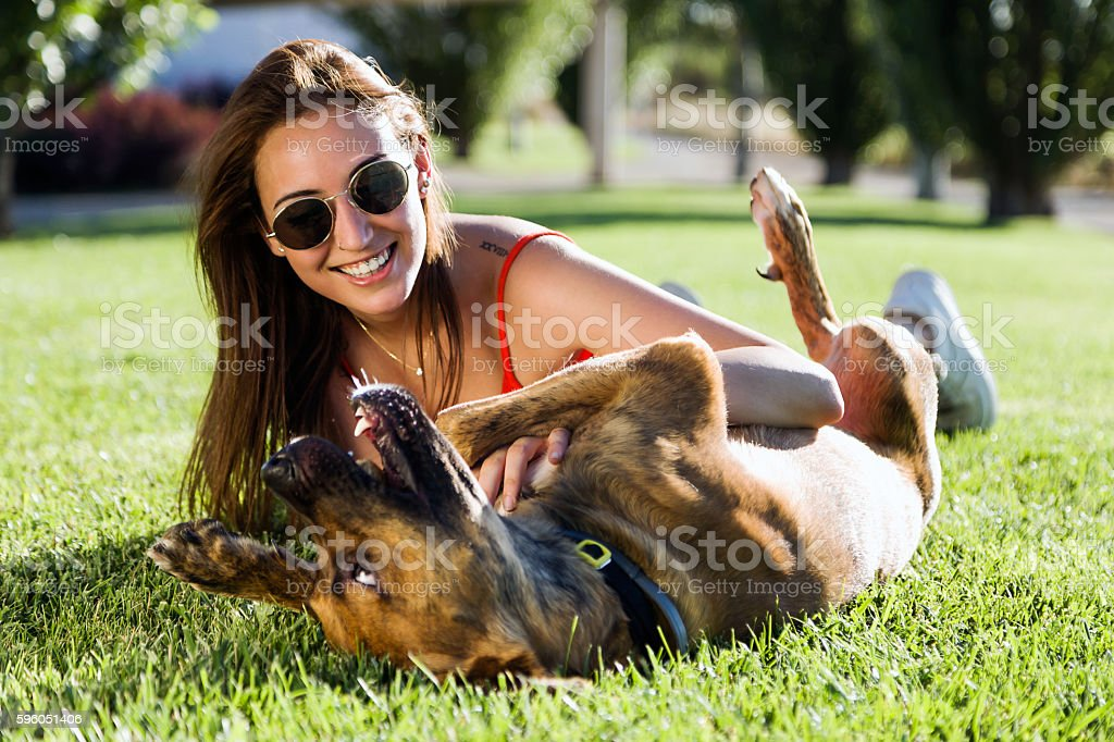 Beautiful young woman playing with her dog in the park. royalty-free stock photo