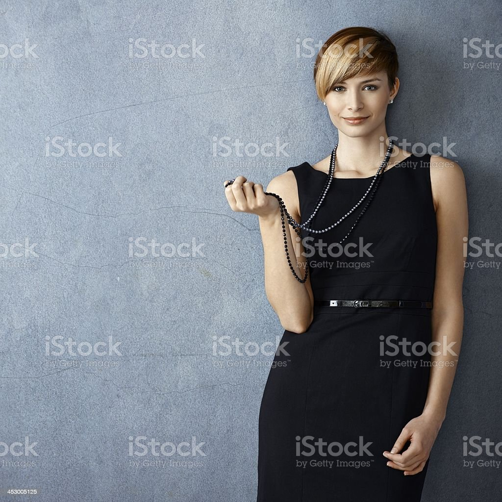 Beautiful young woman playing with pearl necklace stock photo