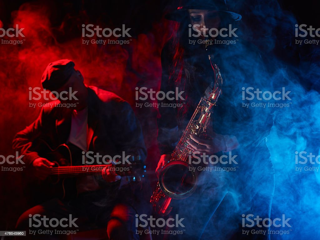 Beautiful young woman plays saxophone stock photo