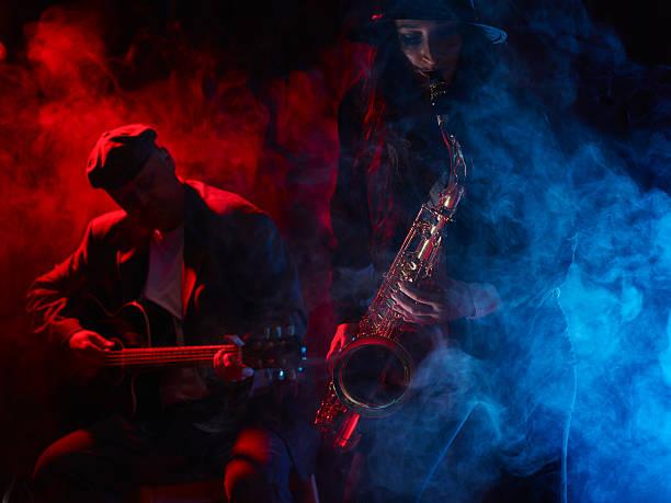 Beautiful young woman plays saxophone stock photo