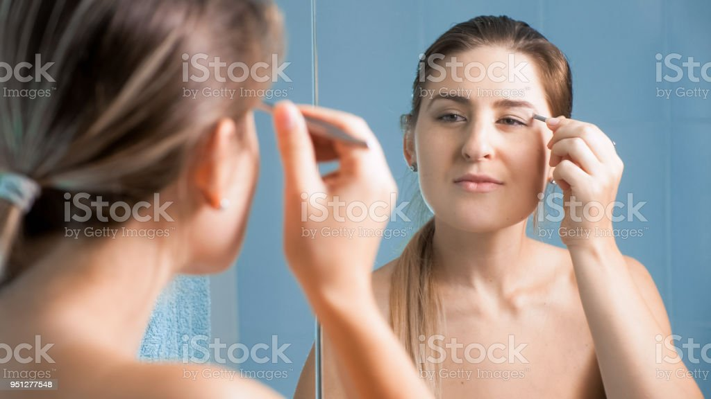 Beautiful Young Woman Plucking Her Eyebrows At Mirror Stock Photo