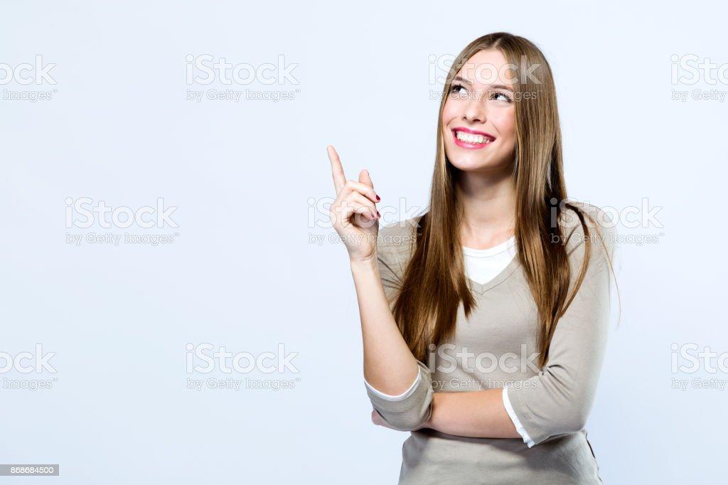 Hermosa joven apuntando hacia arriba sobre fondo blanco. foto de stock libre de derechos