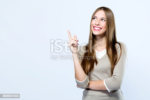 istock Beautiful young woman pointing up over white background. 868684500