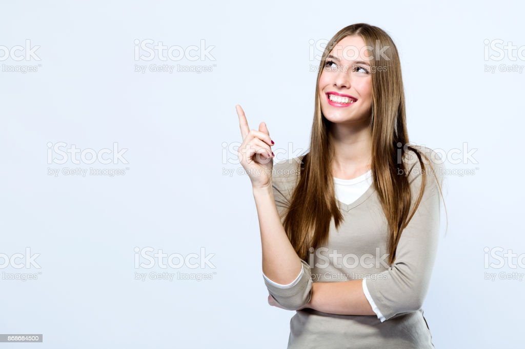 Beautiful young woman pointing up over white background. stock photo