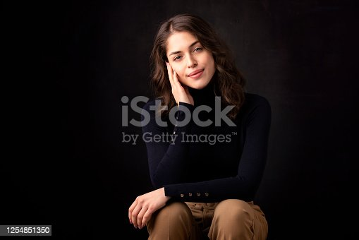 Portrait of beautiful woman wearing turtleneck sweater and smiling while sitting at isolated dark background.
