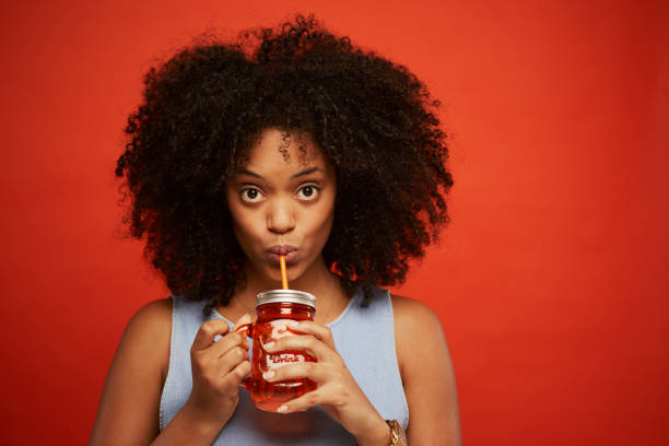 beautiful young woman portrait drinking a smoothie. - drinking juice stock photos and pictures