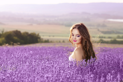 Beautiful young woman portrait in lavender field. Attractive