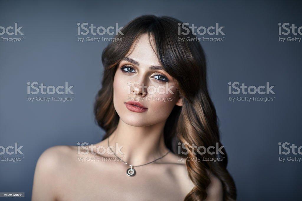 Porträt der schönen jungen Frau mit langen Haaren auf dunklem Hintergrund – Foto