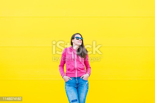 istock Beautiful Young woman posing against vivid Yellow background 1145074152