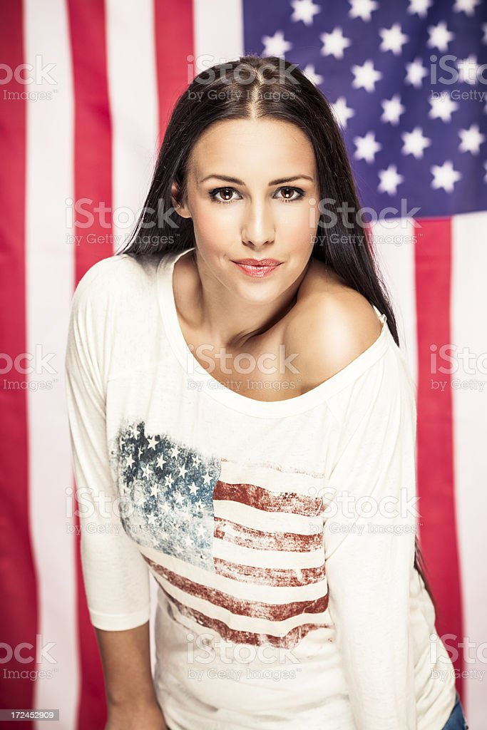 Beautiful young woman posing in front of US national flag stock photo