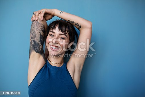 Studio shot of a beautiful young woman posing in sportswear against a blue background. Smiling woman in sportswear with tattoo looking at camera.