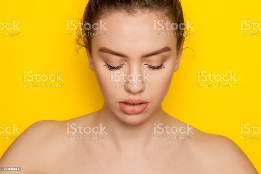 Beautiful young woman posing on yellow background royalty-free stock photo