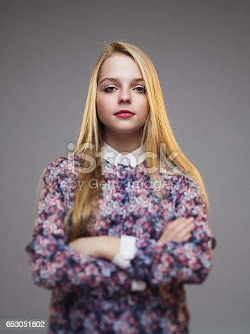 Vertical portrait of beautiful young female model posing with her arms crossed against gray background. Real woman looking at camera with focus on face. Vertical studio portrait.