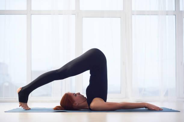 Beautiful young woman practices yoga asana Halasana Plough pose in the yoga studio. stock photo