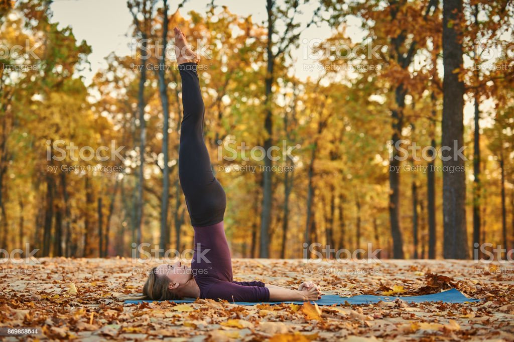 Beautiful young woman practices yoga asana Niralamba Sarvangasana - unsupported shoulderstand pose on the wooden deck in the autumn park. stock photo