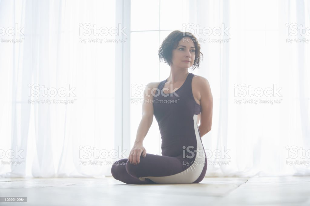 Beautiful Young Woman Practices Yoga Asana Parivrtta Padmasana