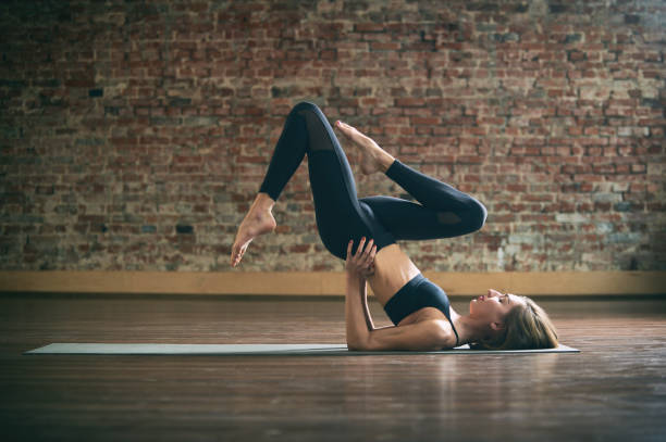 Beautiful young woman practices yoga asana Sarvangasana at the yoga studio on a brick wall background. Beautiful young fit woman practices yoga asana Sarvangasana at the yoga studio on a brick wall background. shoulder stand stock pictures, royalty-free photos & images