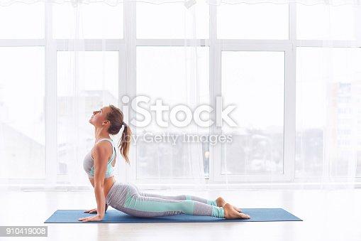 Beautiful young woman practices yoga asana Urdhva Mukha Svanasana - upward facing dog at the bright yoga class with large windows