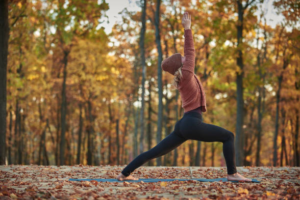 Beautiful young woman practices yoga asana Virabhadrasana 1 - warrior pose on the wooden deck in the autumn park. Beautiful young woman practices yoga asana Virabhadrasana 1 - warrior pose on the wooden deck in the autumn park sun salutation stock pictures, royalty-free photos & images