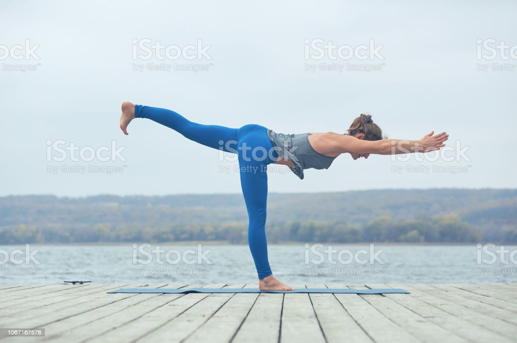 Beautiful young woman practices yoga asana Virabhadrasana 3 - warrior pose 3 on the wooden deck near the lake Beautiful young woman practices yoga asana Virabhadrasana 3 - warrior pose 3 on the wooden deck near the lake. Active Lifestyle Stock Photo