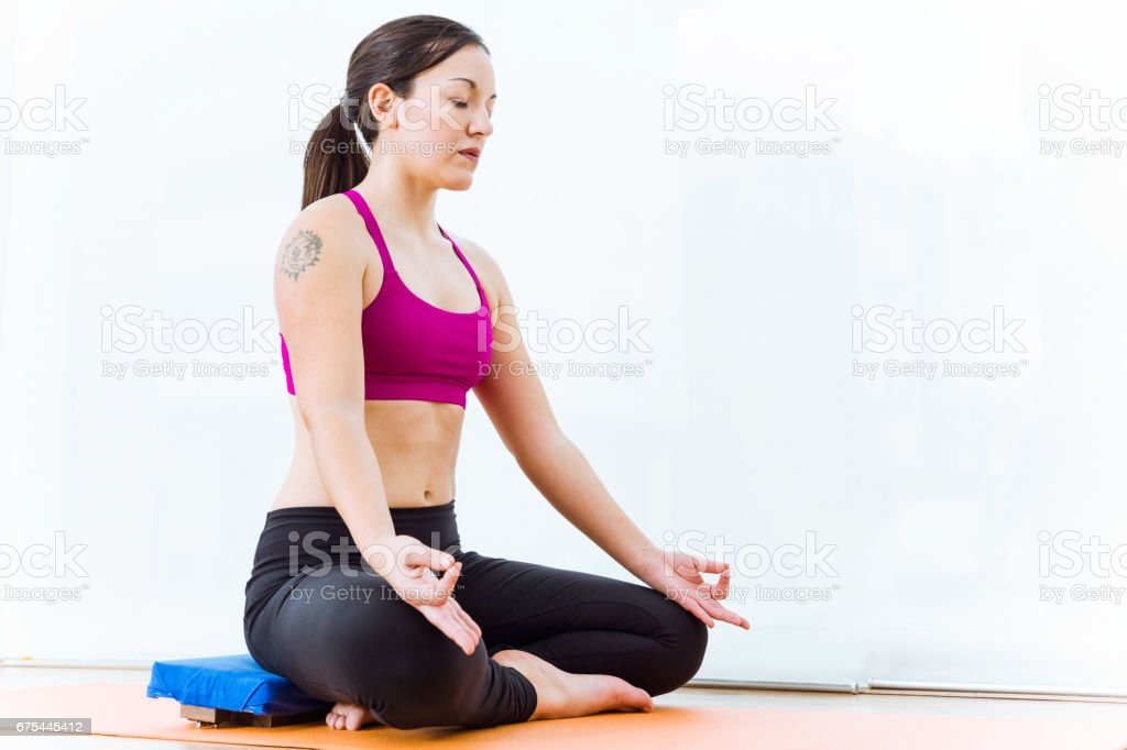 Beautiful young woman practicing yoga at home in the lotus position. photo libre de droits