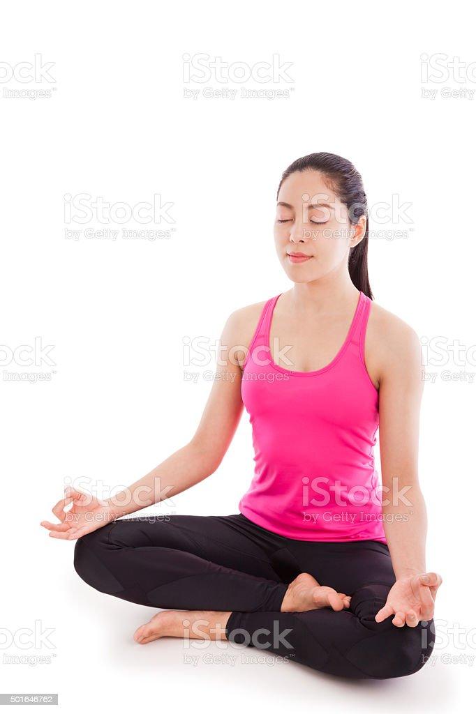 Beautiful young woman practicing yoga, sitting in a lotus positi stock photo
