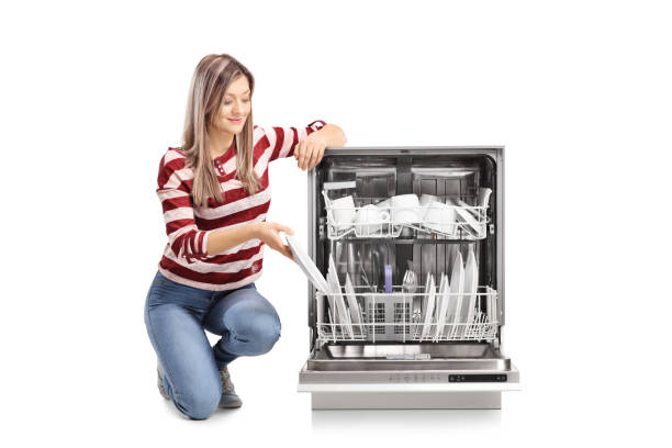Beautiful young woman putting a plate into a dishwasher stock photo