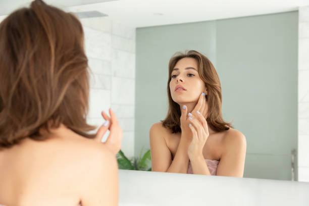 Beautiful young woman putting cream on face skin stock photo