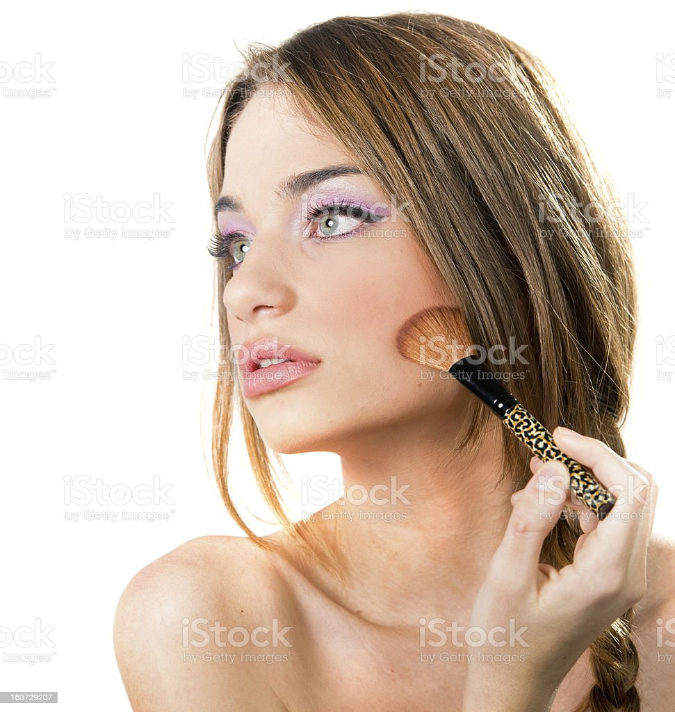 Beautiful young woman putting on makeup,white background royalty-free stock photo