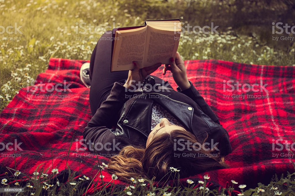 beautiful young woman reading a book in park on grass stock photo