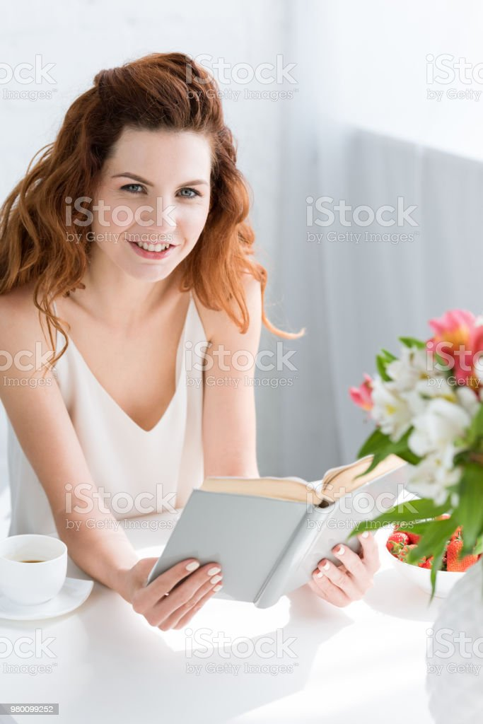 beautiful young woman reading book while sitting at table with coffee cup and flowers in vase stock photo