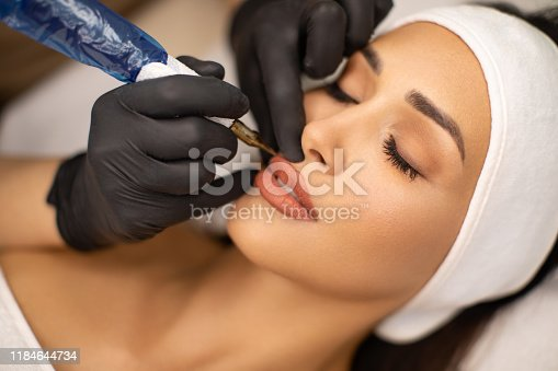 Make up artist applying permanent make up on lips at beauty treatment. Beautician contouring young woman's lips and coloring it with special tool. She do the precise shaping crayon and then microblading.