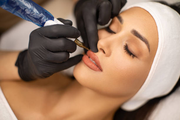 Beautiful young woman receiving permanent make up stock photo