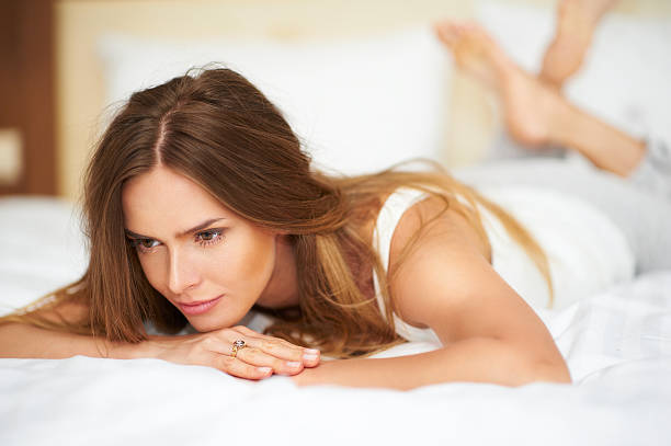 Beautiful young woman relaxing in bed in white casual undershirt stock photo